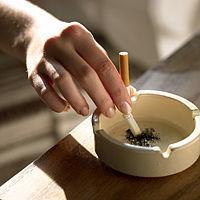 Weibliche Hand zerdrückt Zigarette im Aschenbecher