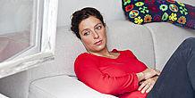 Nachdenkliche Frau sitzt auf Sofa