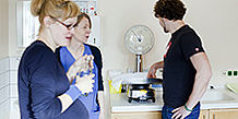 Schwangeres Paar mit Hebamme im Gespräch