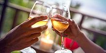 Zwei Personen stoßen mit Weingläsern an