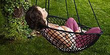 Schwangere liegt entspannt in einem Schaukelsessel