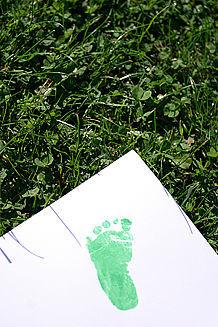 Fußabdruck auf Papier liegt auf grüner Wiese