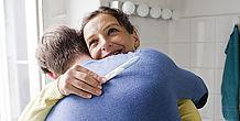 Ein glückliches Paar in einer Umarmung, die Frau hält einen Schwangerschaftstest
