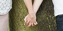 Nahaufnahme: Paar hält Hände vor einem Baum