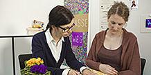 Zwei Frauen, am Tisch, schauen sich eine Broschüre an.
