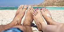 Bild zeigt Frauen- und Männerfüße am Strand
