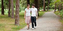 Paar spaziert Arm in Arm durch einen Park