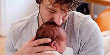 Vater drückt Baby an seine Brust