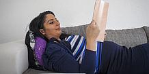 schwangere Frau liegt lesend auf dem Sofa