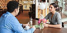 Paar sitzt an einem Tisch im Café und unterhält sich