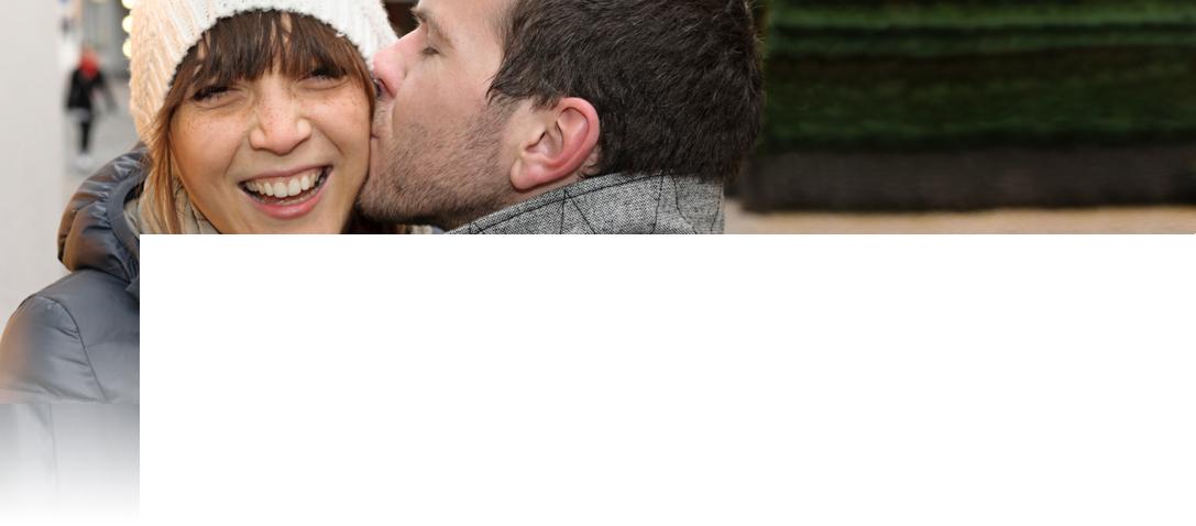 Ein Mann küsst einer lachenden Frau auf die Wange.